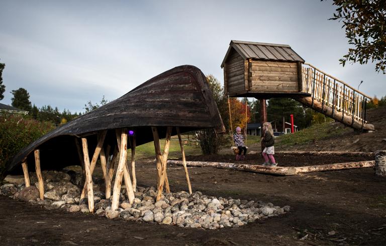 Konstverk bestående av en talande båt och en njalla i trä på en förskolegård