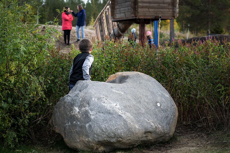 Liten pojke på föreskolegård vid en stol sten