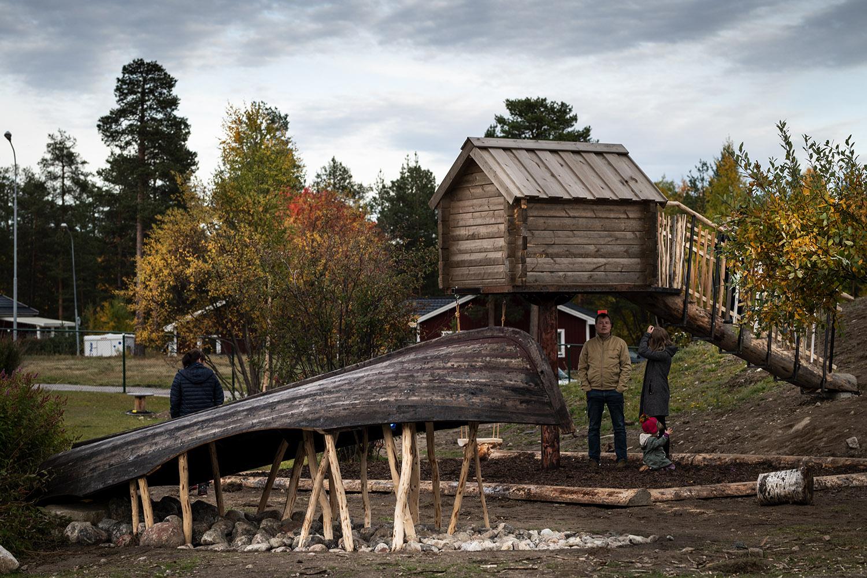 Föreskolegård med en båt uppallad på pinnar till vänster och en bod till höger.