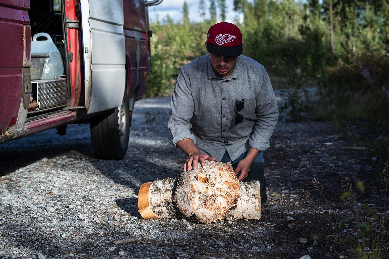 Man i keps undersöker en bit björkträ.