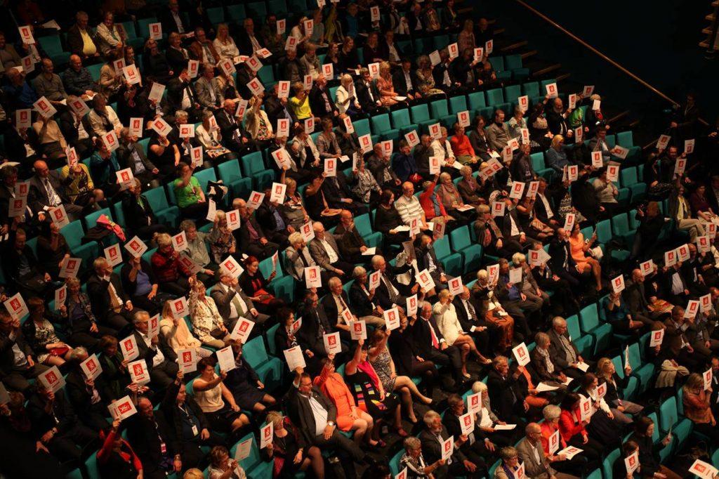 Folk sitter i publik och håller upp lappar.