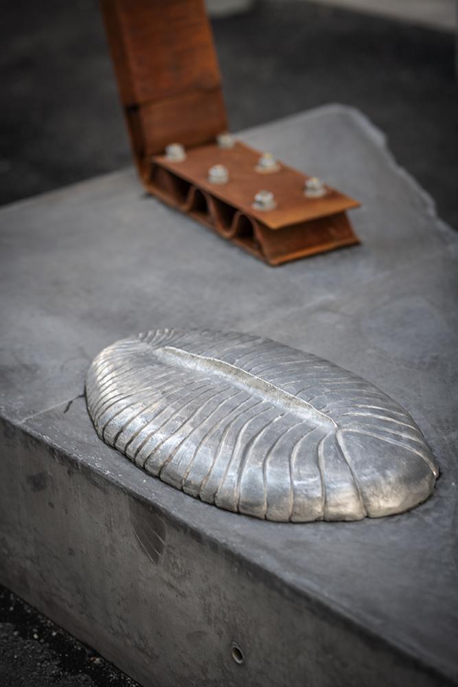 Detalj av metall som ser ut som en fossil på ett underlag av sten.
