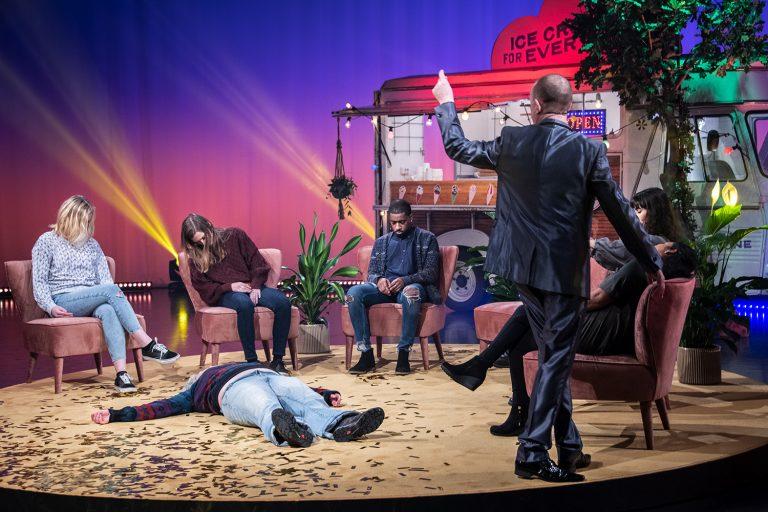 En man står bland en grupp människor och har hypnotiserat dem.