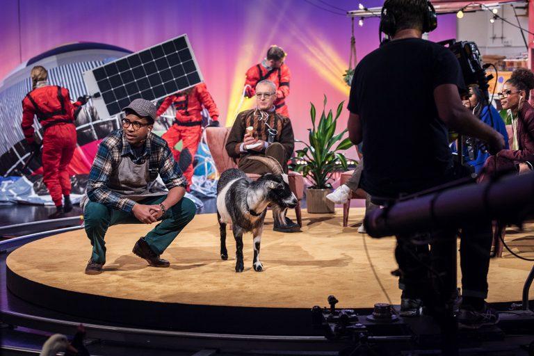 En man och en get filmas i en tv-studio.