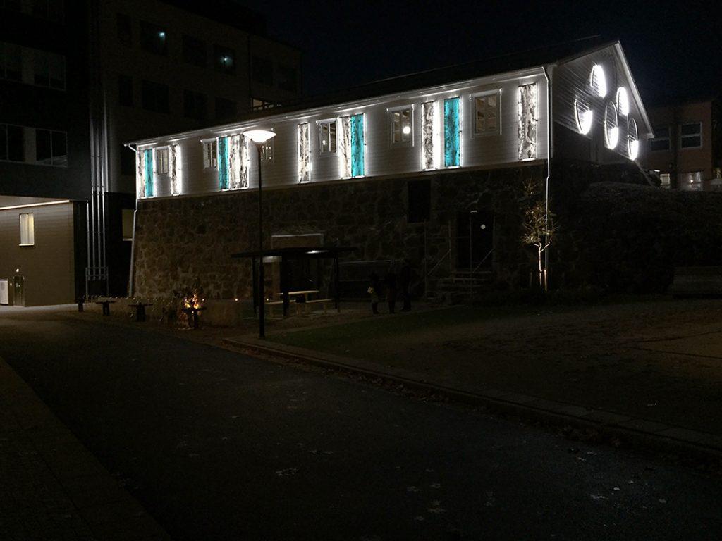 Mot långsidorna på Ismagasinet sitter upplysta corianplattor i verket Correlation. Gaveln lyses upp av ljusbågar.