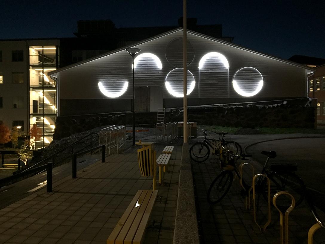 Under dygnets mörka timmar lyser ljusbågarna på gaveln av Ismagasinet och skapar ett nytt mönster.
