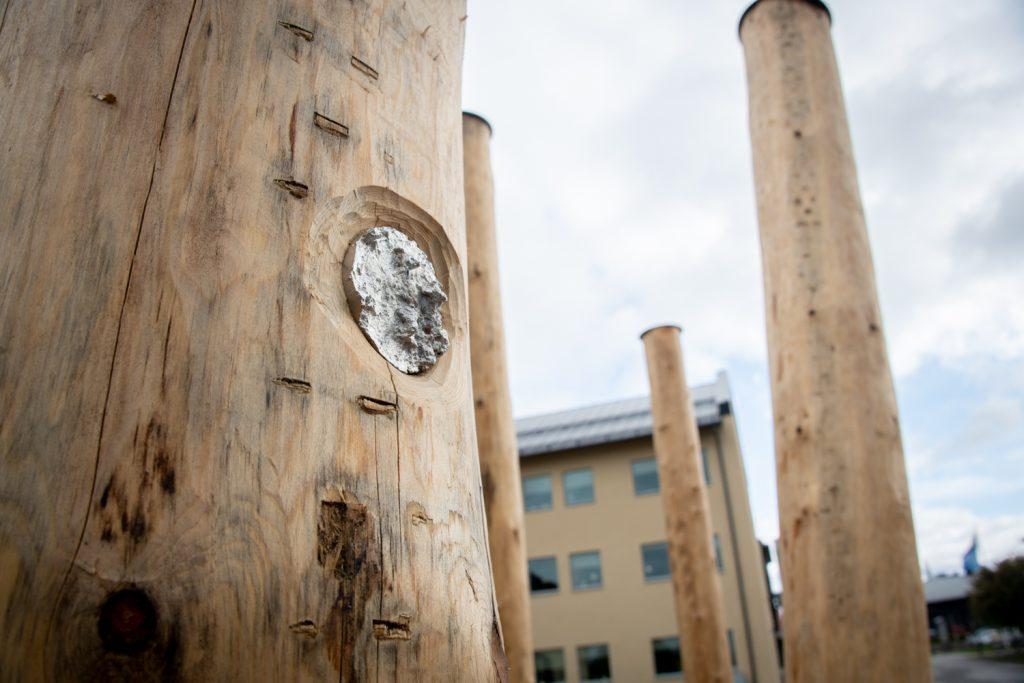 Detaljbild av en trästolpe med snidat mönster och metalldetaljer.