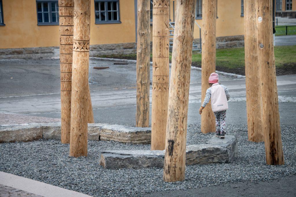 En liten flicka leker bland stammarna i Katarina Pirak Sikkus konstverk.
