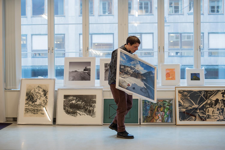 En man bär och tittar på ett konstverk. Tavlor står radade under fönster i bakgrunden.