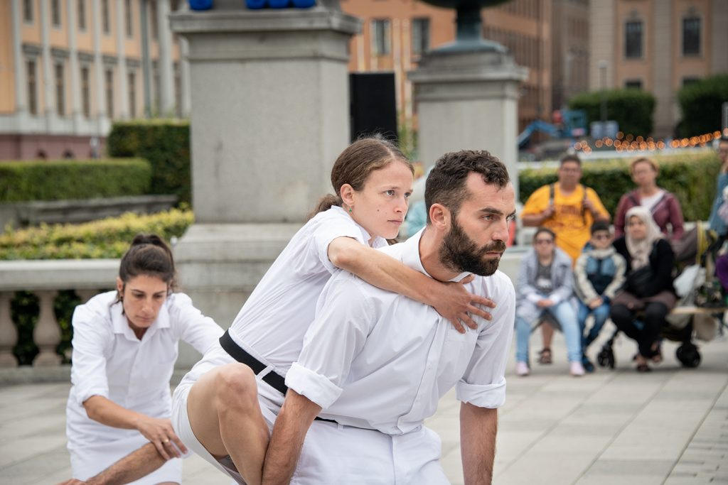 Kvinna blir buren av en man, båda har vita kläder