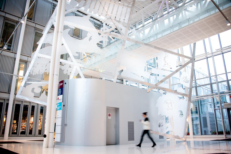Bild på entréhall med en stor glasskiva med frostade figurer.