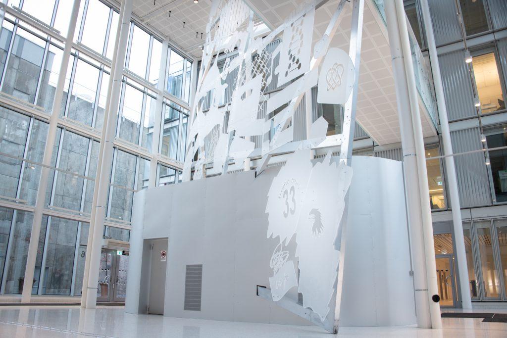 Hög glasskiva med frostat mönster i en entréhall i ett stort hus.
