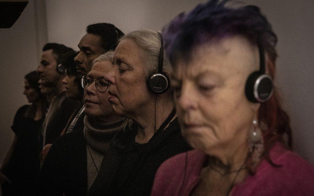 En rad människor står med hörlurar i en hall.
