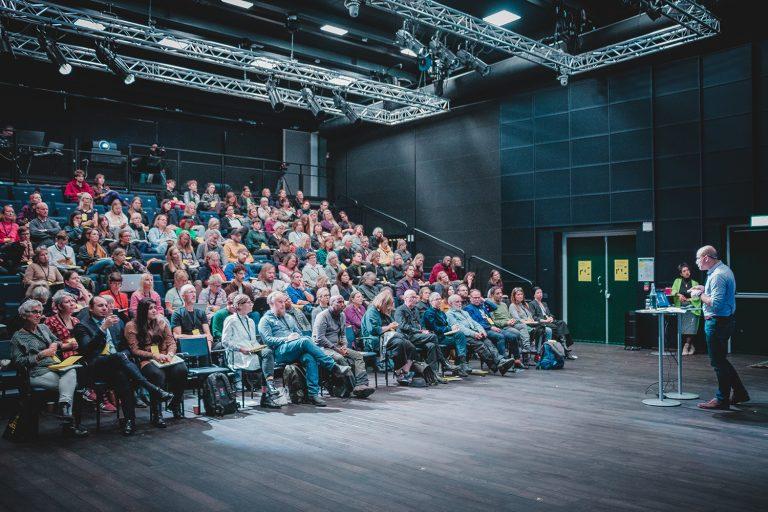 Talare på scen framför gradäng full med folk.