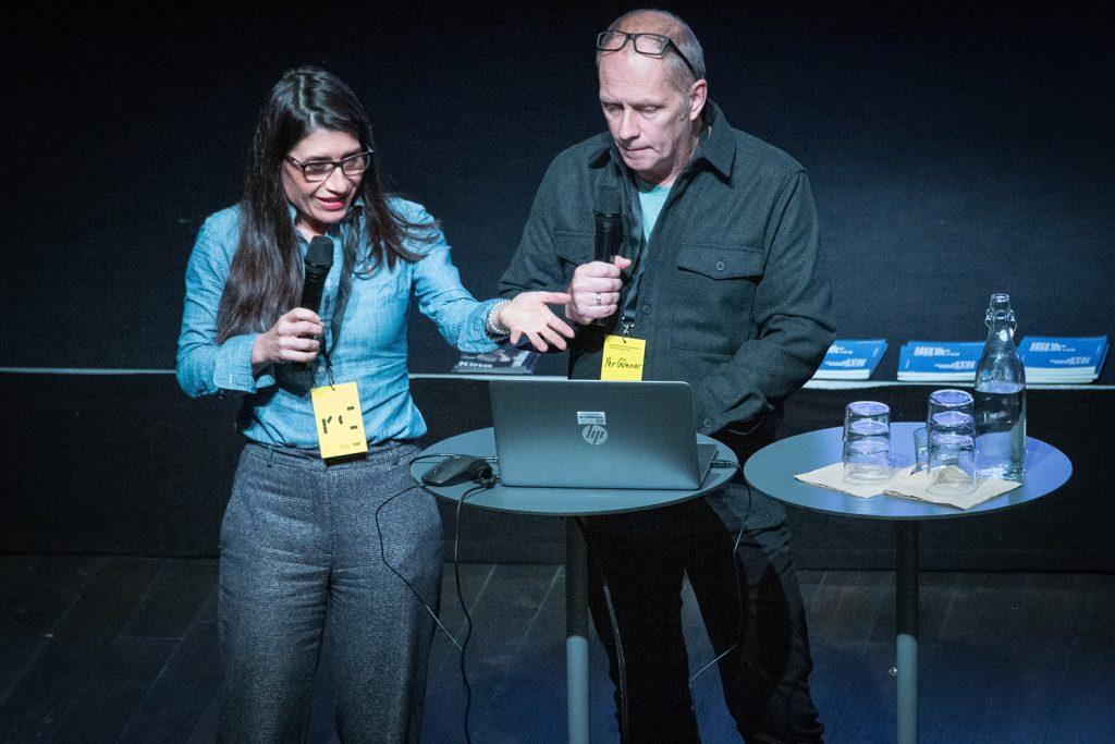 En kvinna och en man står vid ett ståbord och pratar i mikrofoner.