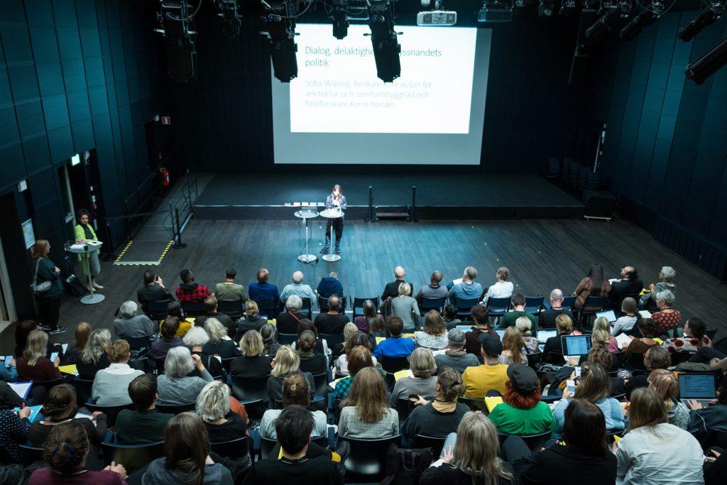 En kvinna står längst fram framför en skärm och håller ett föredrag