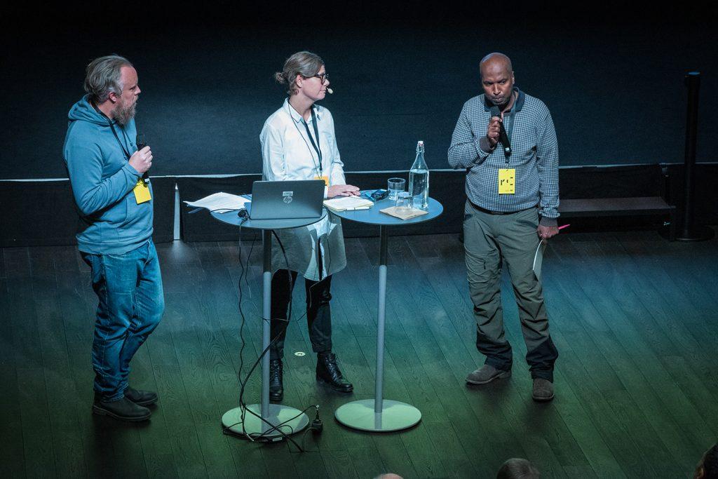 Tre personer samtalar på en scen