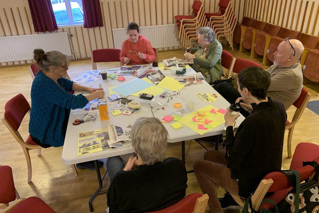 En grupp människor sitter runt ett bord med massor av papperslappar framför sig.