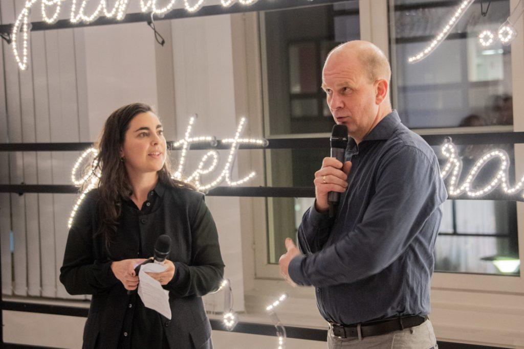 Två personer håller ett tal framför en ljusskylt
