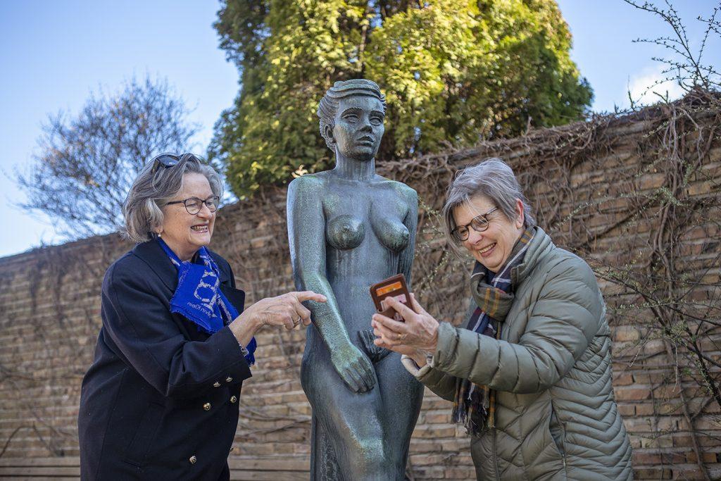 Två damer tittar i en telefon framför en staty