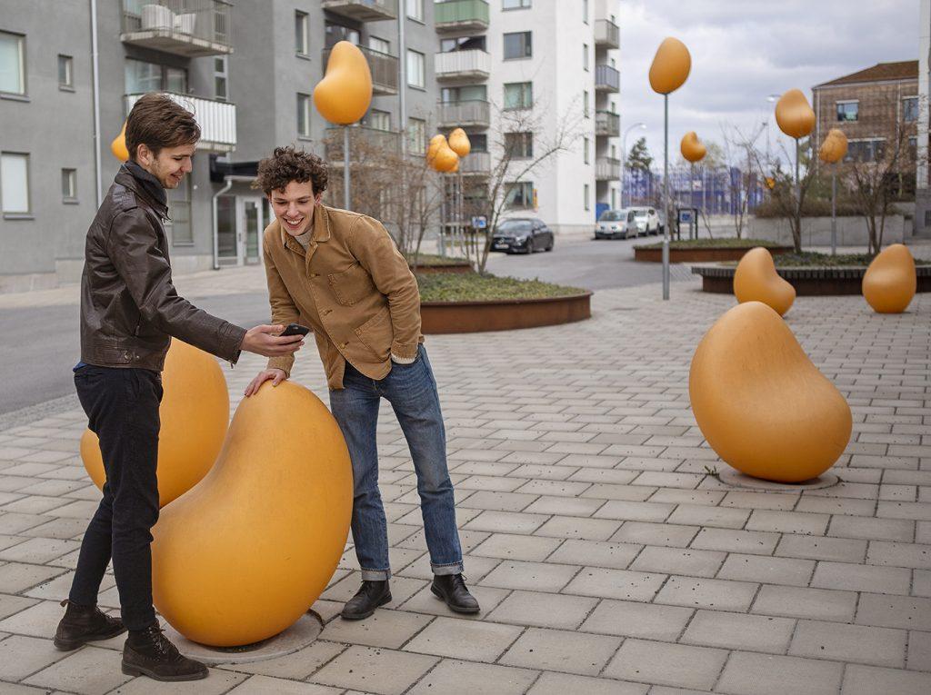 Två yngre män tittar i en telefon bland skulpturer utomhus.