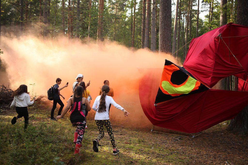 En grupp barn springer omkring i skogen kring en tygskulptur.