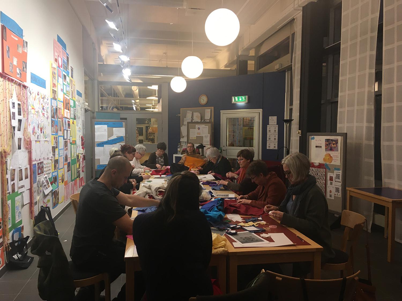 En samling personer sitter kring ett bord och arbetar.