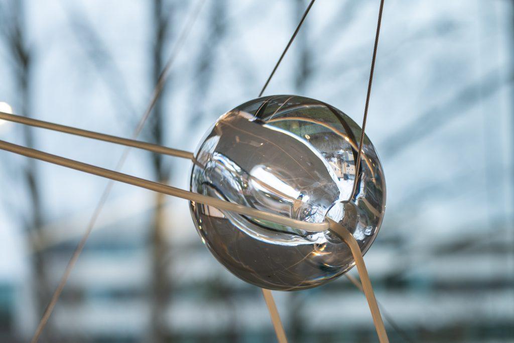 Handbllåsta glaskulor som svävar i gummitrådar i ett trapphus