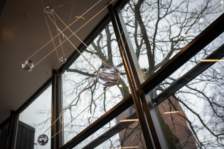 Handbllåsta glaskulor som svävar i gummitrådar i ett trapphus.