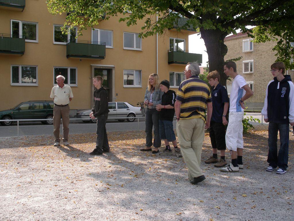 En grupp människor spelar boule utomhus.