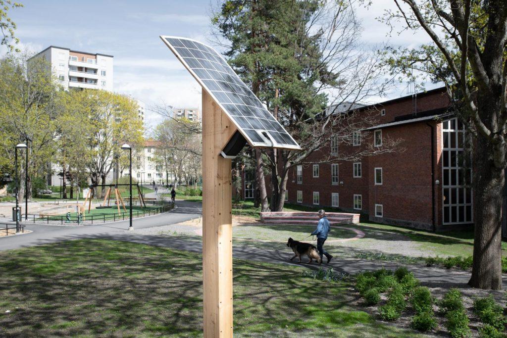 En trästople har en solcell på toppen. I Bakgrunden går en kvinna förbi med en hund.