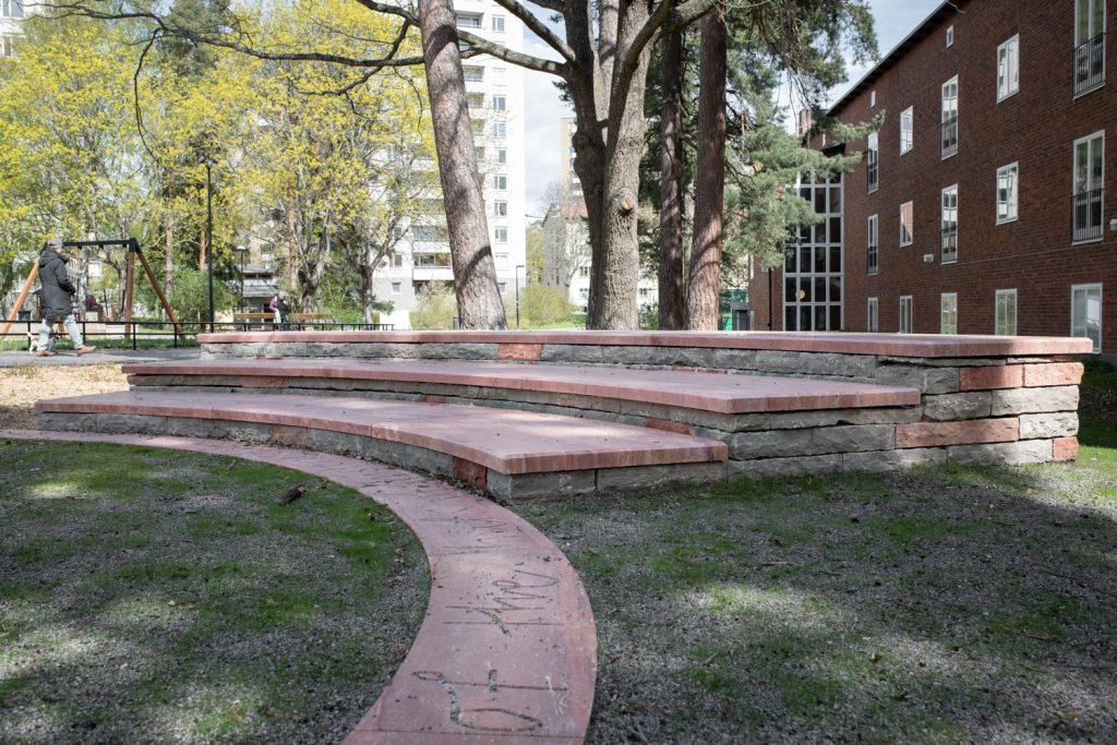 En murad bänk med stenskiva högst upp. I bakgrunden är det en skolbyggnad.