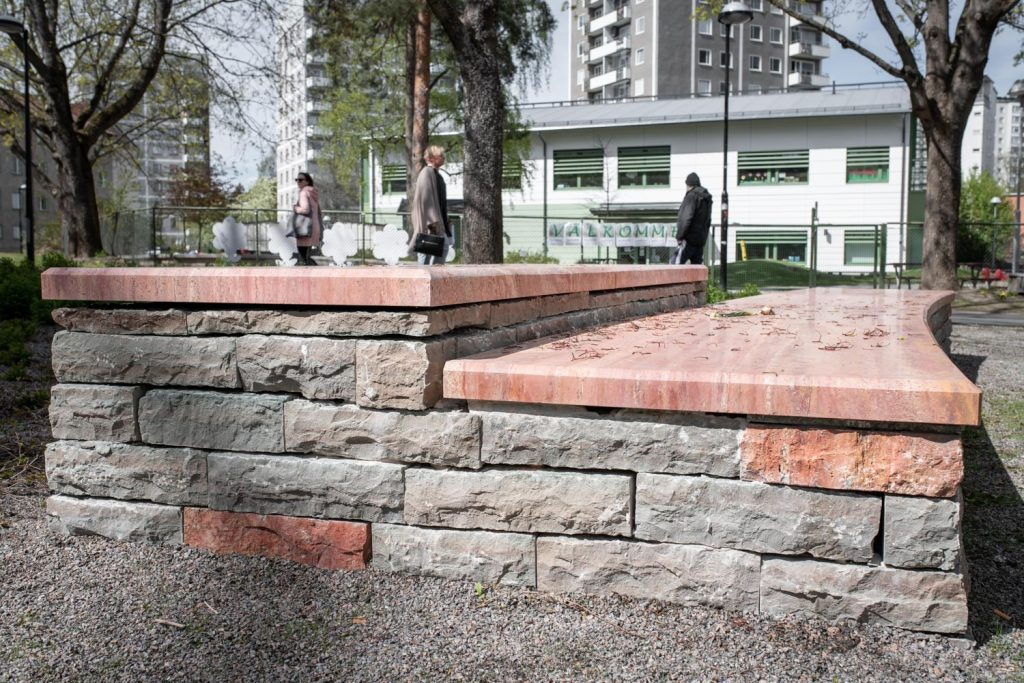 Detalj av en murad bänk med stenskiva högst upp. I bakgrunden går människor på en gångstig.