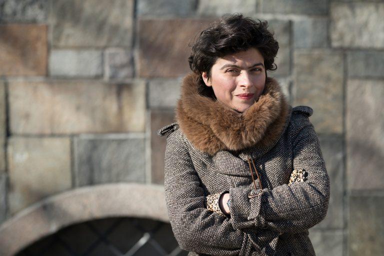 Kvinna står och tittar rakt in i kameran. Hon har en vinterkappa på sig. En stenmur i bakgrunden.