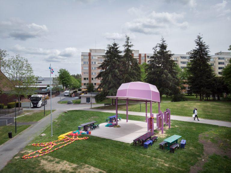 PÅ en gräsmatta står en paviljong som ser ut som en stor rosa keps.