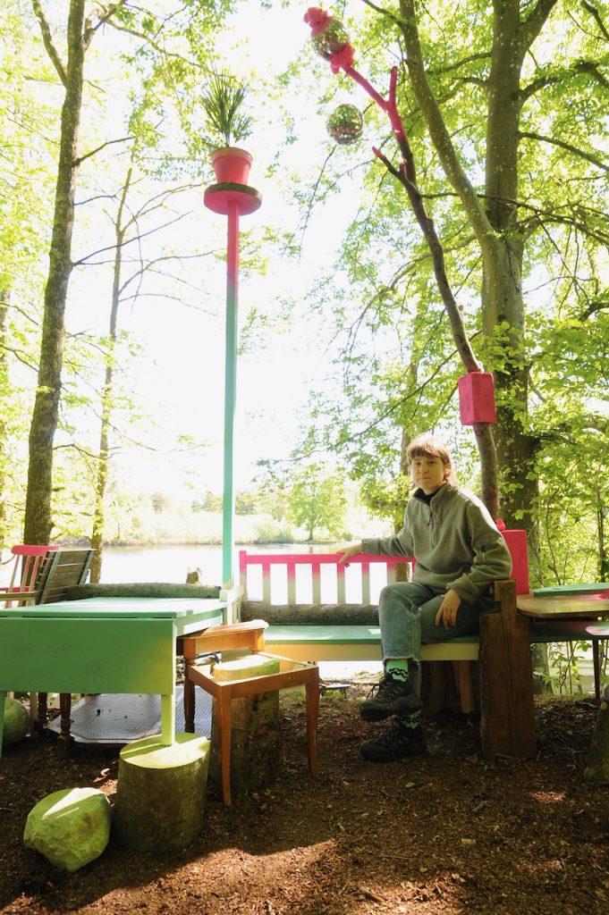 En kvinna sitter i ett vardagsrum i en skog