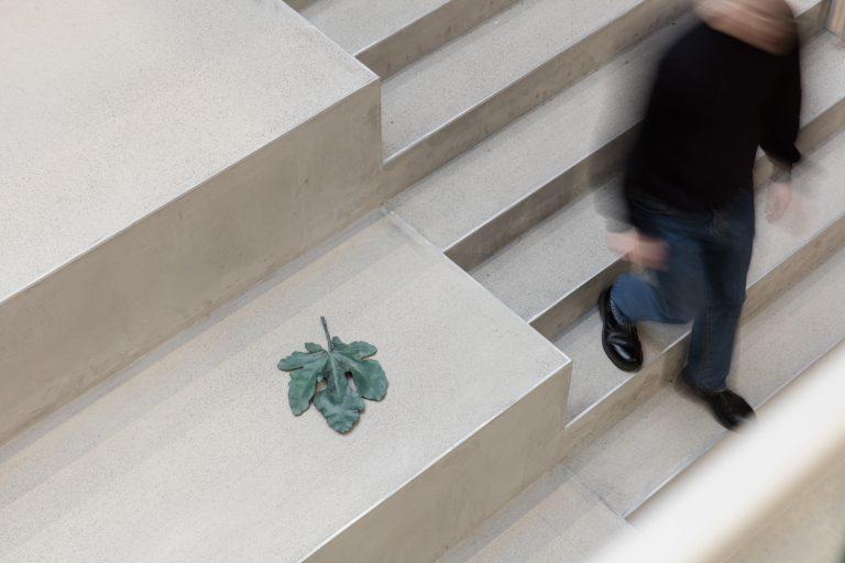 En man går ner för trappan och till höger ligger Meriç Algüns konstverk The Orchard of Resistance. Ett grönt delikat blad.