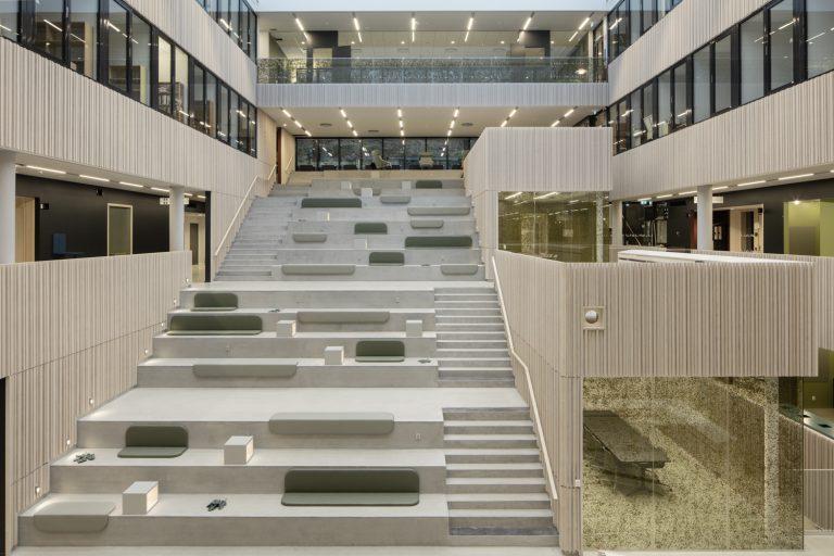 Foto på nya byggnaden Humanisten i Göteborg. En stor trappa i ljust trä med sittplatser. Kuddar och ett verk utformat som blad är utplacerat på den stora trappan.