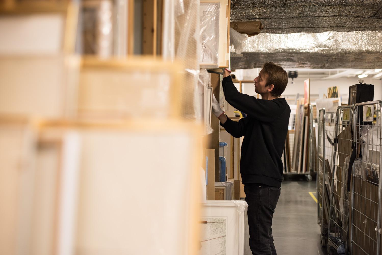 En man i gakgrunden arbetar med hyllor där det står tavlor.