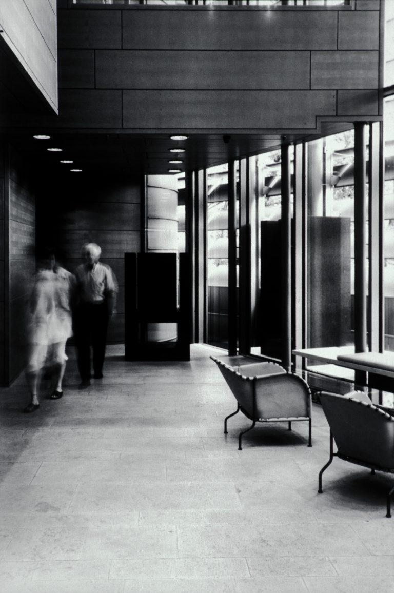 Interiörbild från långsmalt rum med en glasvägg, stolar och en skulptur