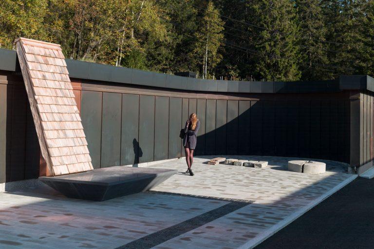 En tegelvägg står lutad mot ett hus. Den vilar på ett stenfundament. Det står en person bredvid skulpturen.