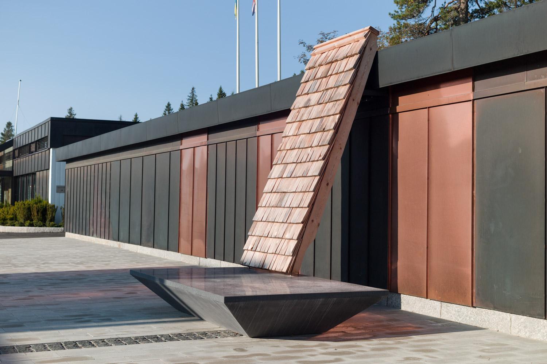En tegelvägg står lutad mot ett hus. Den vilar på ett stenfundament.