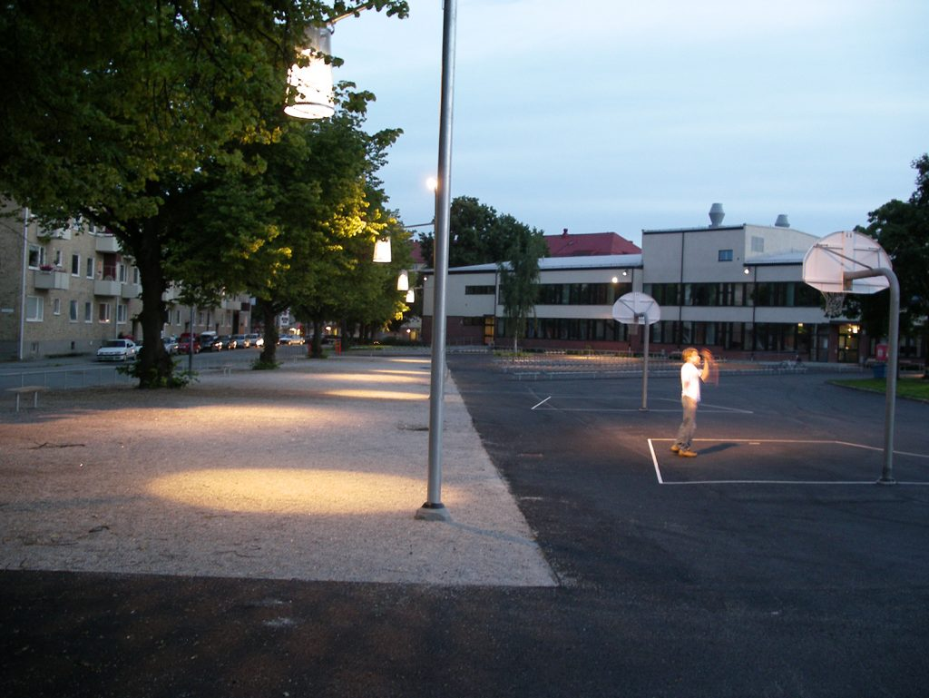 Lampor lyser upp en skolgård där en ensam person spelar basket.