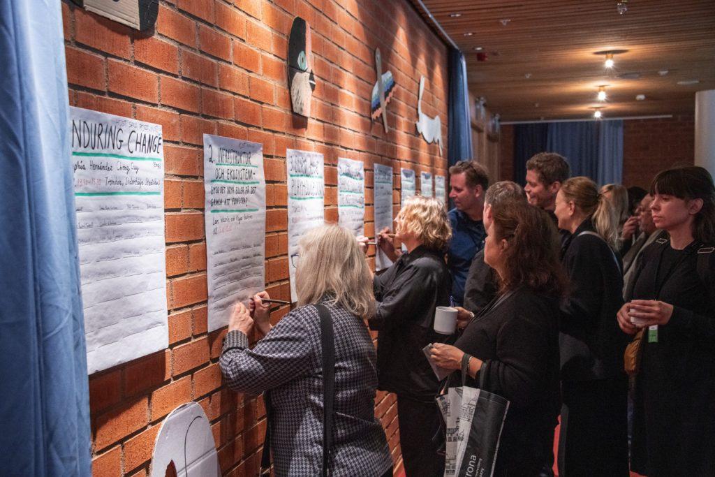 En grupp människor står och tittar på en rad papper uppklistrade på en tegelvägg.