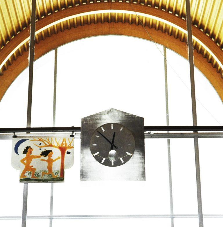 Mikael Richter, Apollo och Dafne, 2001. Målning i emalj/klockhus i aluminium/figur i neon. Målningen rör sig i en bana (84m) runt entréhallen ett antal gånger per dag. Mellan turerna finns den i klockhuset