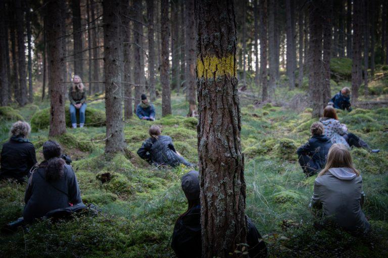En grupp människor sitter på huk i en mossig och murrig skog