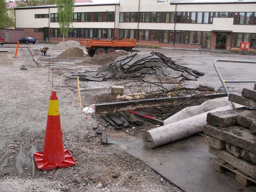 En skolgård där man rivit bort asfalt. En kon står i förgrunden.