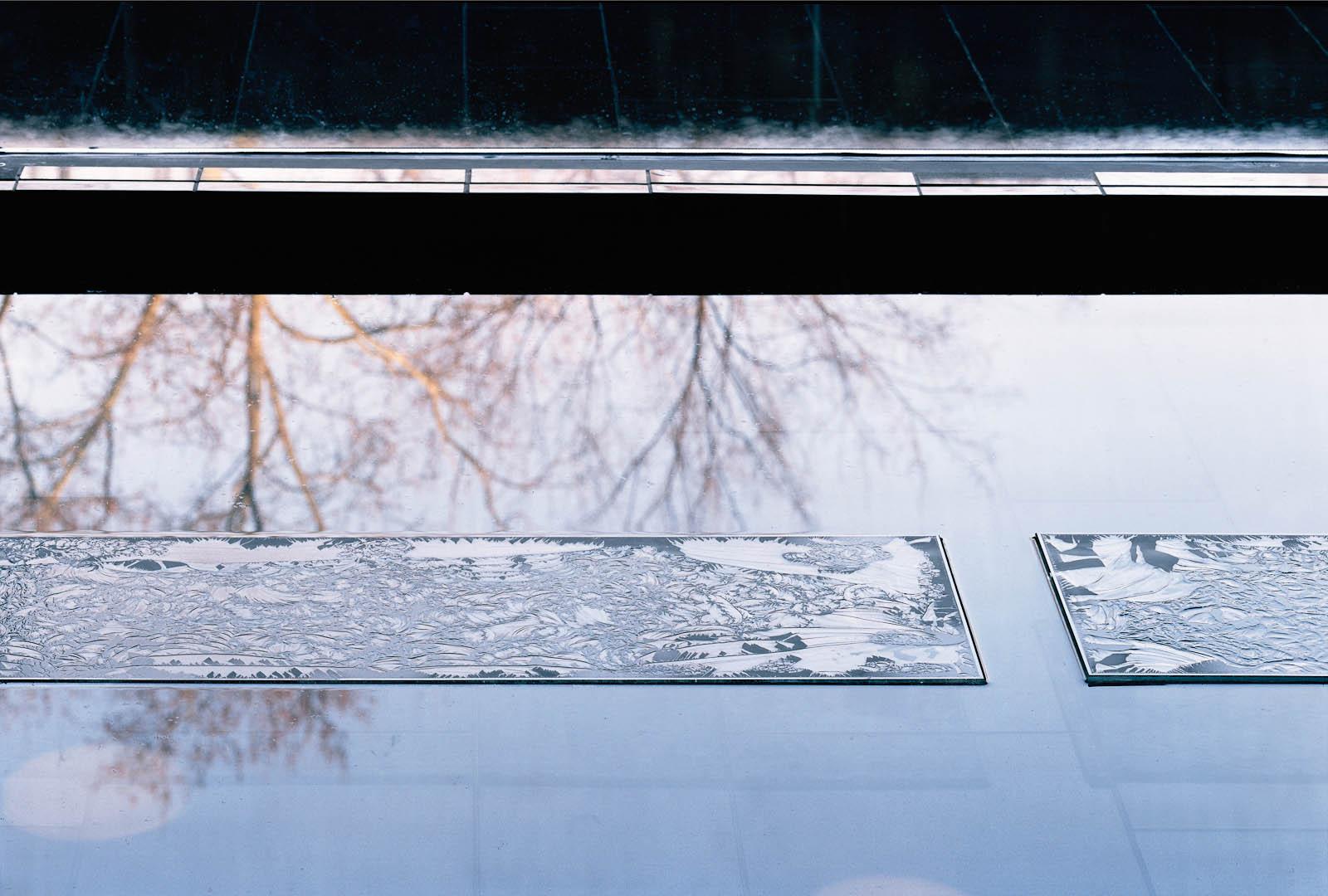 Frostig rektangulär glasskiva som ligger i en vattenspegel.