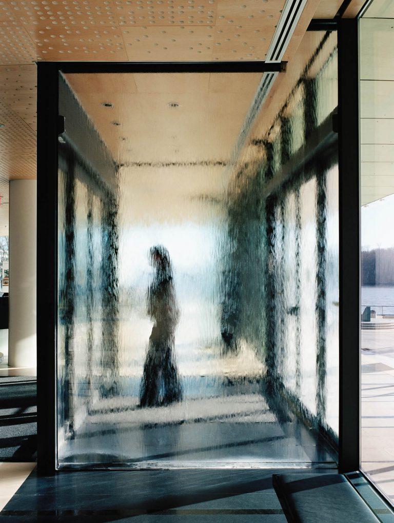 Person som går igenom entre av glas som det ser ut som att det rinner vatten nedför