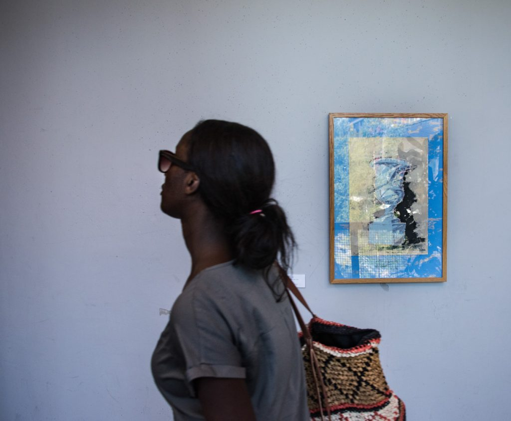 Kvinna går förbi en målning som hänger på en vit vägg